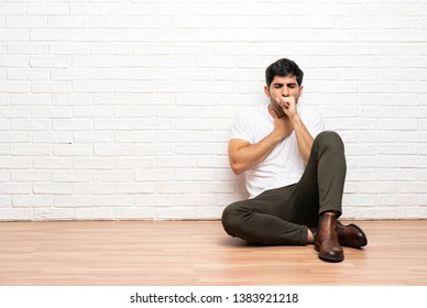 Young man sitting on the floor is suffering with cough and feeling bad