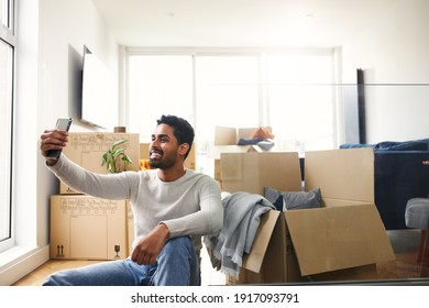 Young man sitting on floor in lounge of new home using mobile phone to make video call with friends and family as he unpacks removal boxes