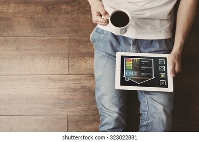 Young man sitting on floor with tablet and cup of coffee in room