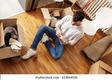 Young man sitting on floor and using tablet  in his new apartment.He relaxing after cleaning and unpacking.