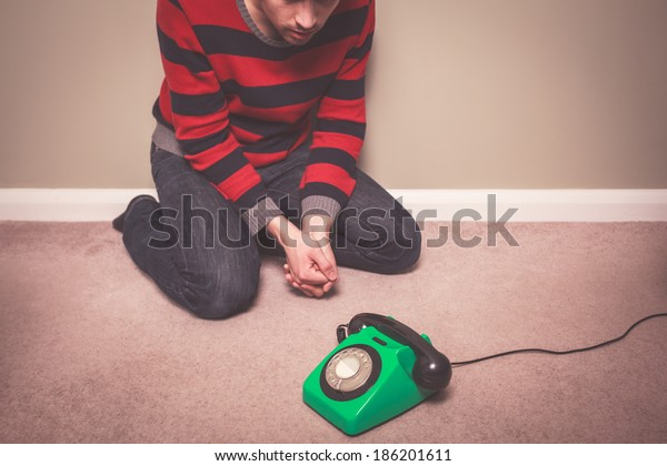 A young man is sitting on the floor and is desperately waiting for a phone call
