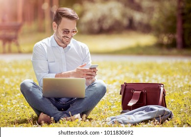 Young man is sitting on the grass in park with his laptop. Freelance working concept. He write a message on the phone.