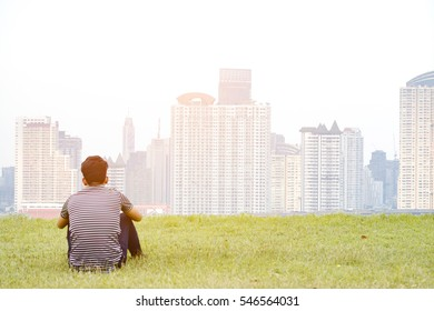 A young man sitting on the grass on vacation. Background building concept healthy soft focus.