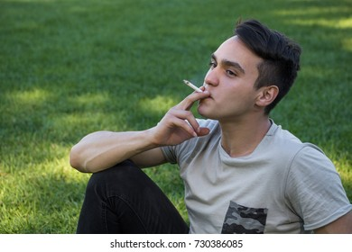 Young man sitting on the grass is smoking cigarette and listening to music
