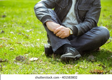 Young man sitting on green grass in the park. Early spring in the park