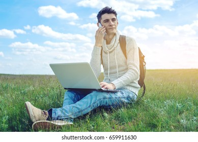 Young man sitting on a green meadow with laptop and talking on the phone on the background of blue cloudy sky. The concept of education and work with nature