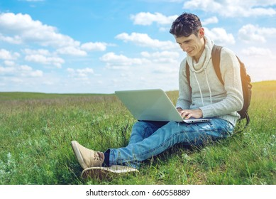 Young man sitting on a green meadow with laptop wireless on the background of blue cloudy sky. The concept of education and work with nature