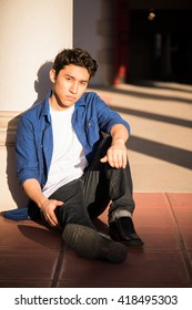 Young man sitting on the ground, leaning against a pillar in a courtyard,