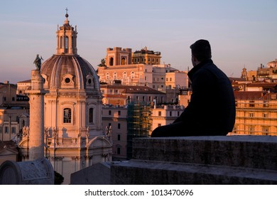 Young man sitting on high, looking at The Church of the Most Holy Name of Mary at the Trajan's Column.
