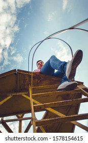 Young man is sitting on high iron construction looking in front of the sky