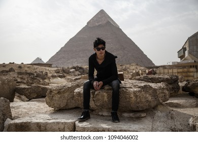 Young man sitting on a huge rock in the pyramids of Giza the great pyramid showing behind him in the background.