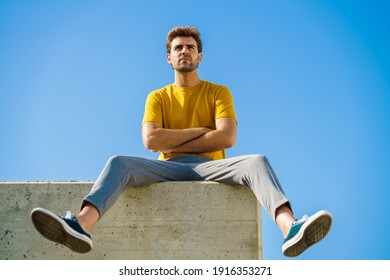 Young man sitting on a ledge looking around