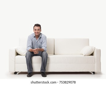 young man sitting on a modern sofa.isolated on white.photo with copy space