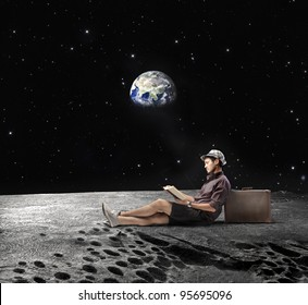 """Young man sitting on the Moon and reading a book with Earth in the background """"Elements of this image furnished by NASA"""""""