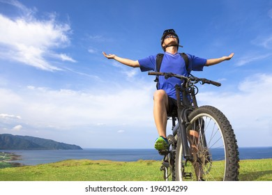 young man sitting on a  mountain bike and open arms to relaxing