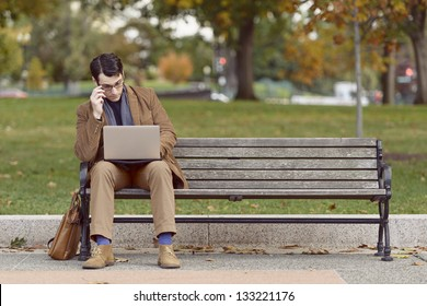 Young Man Sitting On Park Bench, Looking Bored With His Work