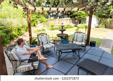 Young man sitting on patio lounge chair in outdoor spring flower garden in backyard of home zen with water fountain, pergola canopy gazebo, table, plants, sofa