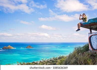 Young man sitting on pillbox over looking Lanikai takking a cell