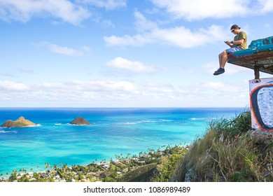 Young man sitting on pillbox over looking Lanikai texting on a cell phone loving sitting on top of the world
