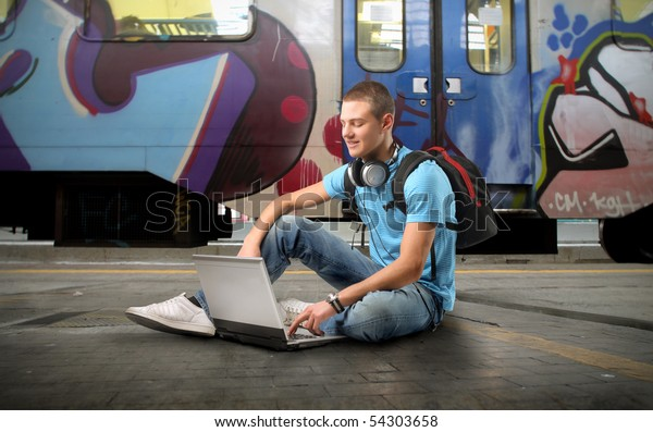 Young man sitting on the platform of a train station and using a laptop