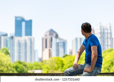 Young man sitting on railing in Piedmont Park in Atlanta, Georgia looking back on scenic cityscape skyline of urban city skyscrapers downtown