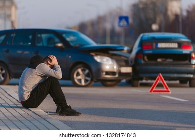 A young man is sitting on the road and looking shaken after the car accident