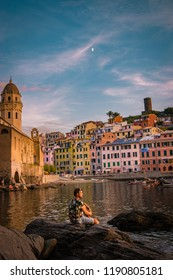 young man sitting on a rock by the harbour front watching sunset Vernazza Cinque Terre Italy, sunset harbor front ocean man looking at sea