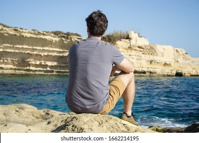 Young man sitting on a rock by the sea. Summer vacation. Mediterranean Sea.