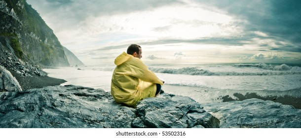 Young man sitting on a rock on a rocky beach watching the ocean in a yellow rain coat Location: Hualien County, Taiwan