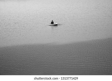 Young man sitting on a round shape concrete boat in a pond