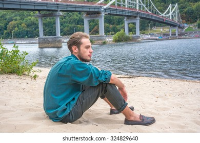 Young man is sitting on the sand near a river