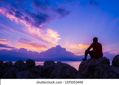 Young man sitting on sea rocks by the beach thinking, contemplating, determining the way forward. Life changing decisions. Priority decision making. Freedom to choose. Passing time as the sun sets.