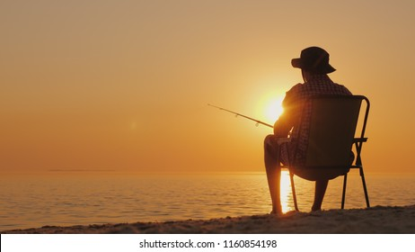A young man is sitting on the seashore, fishing. Relaxing in the open air