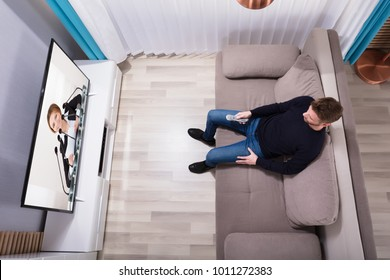 Young Man Sitting On Sofa Watching Television At Home