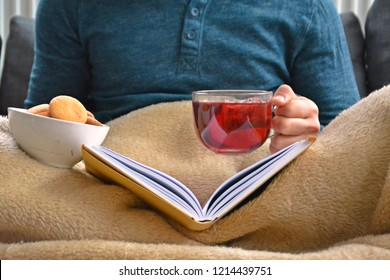 A young man is sitting on a sofa and reading a book while holding a fruit tea in a glass cup in hand and biscuits stand beside him - closeup on the book and glass cup full of tea - concept to warm up