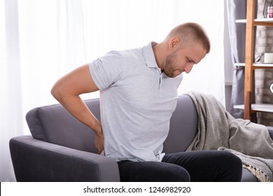 Young Man Sitting On Sofa Suffering From Back Pain