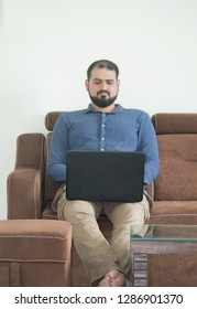 Young man sitting on sofa and using laptop at home