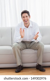 Young man sitting on sofa applauding and smiling at camera