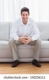Young man sitting on sofa smiling at camera