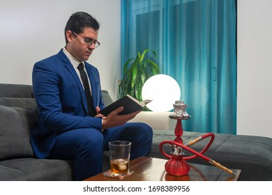 Young man sitting on a sofa. He is wearing a blue suit. He's reading a book. On a wooden table there is a glass of whiskey and a red shisha.