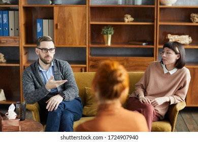 Young man sitting on sofa with his wife and talking to their family psychologist at office