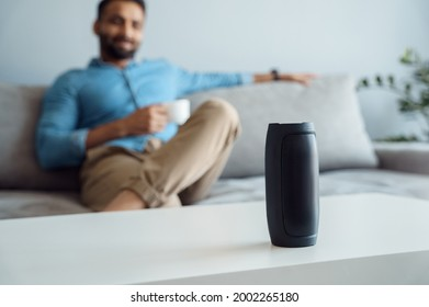 Young man sitting on sofa at smart home listening small portable wireless speaker. Focus on virtual voice digital sound assistant on table. Indian businessman using mini bluetooth stereo gadget