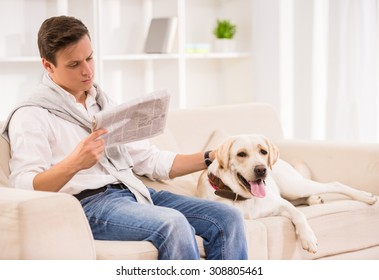 Young man is sitting on sofa with dog and reading a newspaper.