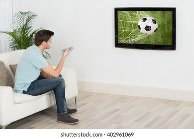 Young Man Sitting On Sofa Watching Football Match On Television