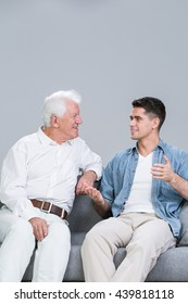 Young man sitting on a sofa with his grandfather, talking and smiling, light background