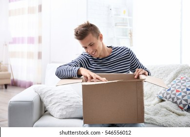 Young man sitting on sofa and unpacking received parcel
