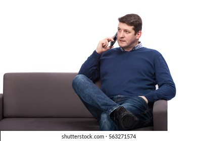 Young man sitting on sofa and talking on phone, isolated on white