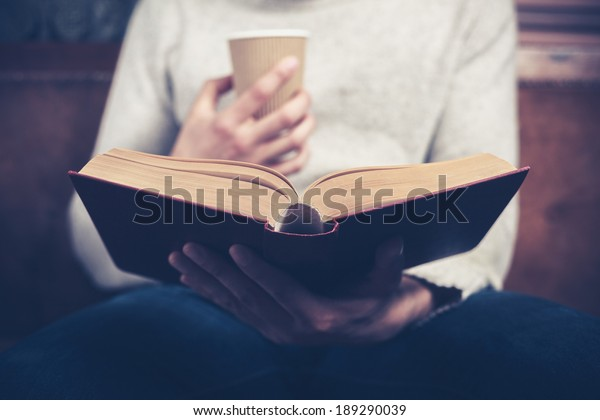Young man is sitting on a sofa and reading a book while holding a paper cup