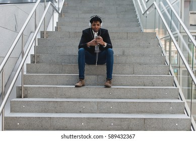 Young man sitting on stairs and listening to music while phone browsing. Horizontal indoors shot.