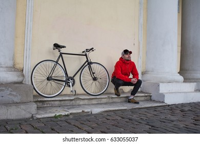 young man sitting on stairs of old building  , black hipster bicycle on background